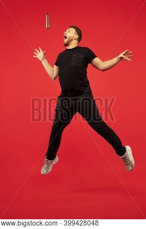 Singing Like Rockstar. Full Length Portrait Of Young High Jumping Man Gesturing Isolated On Red Stud