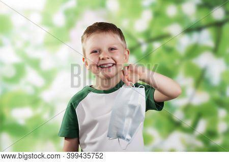 Happy Little Boy Smiling And Holding Face Mask In Hand On Green Background