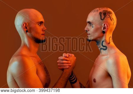 Portrait Of Young Twin Brothers With Tattoos And Piercings Looking At Each Other, Holding Hands, Sta