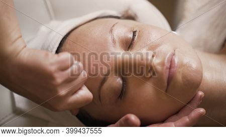 Professional Anti-aging Facial Massage. Action. Relaxing Facial Treatment At Spa. Relaxing And Rejuv