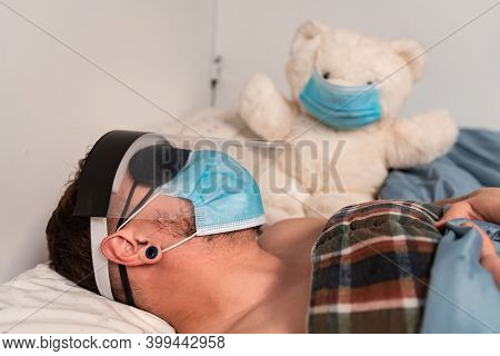 Side View Of A Man And His Big White Teddy Bear In Bed, Both Wearing Face Mask. Man Wears Sleeping M