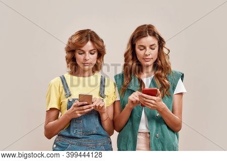 Two Attractive Young Girls, Twin Sisters In Casual Wear Texting, Using Smartphone App While Standing