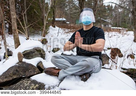 Full Shot Of Young Man In T-shirt Sitting On The Edge O Fa Lake In The Snow, Wearing Covid Mask And