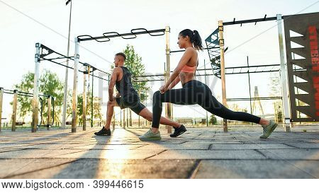 Young Fit Man And Girl Doing Lunges Exercise While Standing Sideways To Camera During Workout On Urb