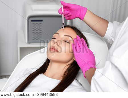 Cosmetologist Makes Rejuvenating Anti Wrinkle Injections On The Face Of A Beautiful Brunette Woman.