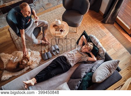 Cozy Family Tea Time. Father And Son In The Home Living Room. Men Petting Their Beagle Dog And. Boy