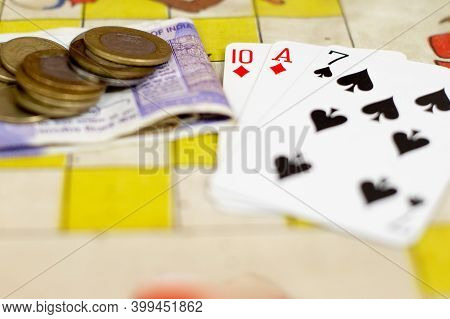Table With Cards And Indian Currency Note And Coins Placed Showing Gambling Going On In Family And F