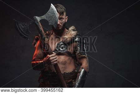 Armed With Huge Two Handed Axe Nordic Barbarian In Light Armour In Dark Background.