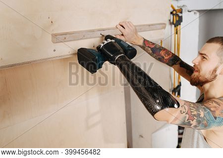 Crafty Cyborg Man With Bionic Hand Working With Cordless Electric Screwdriver