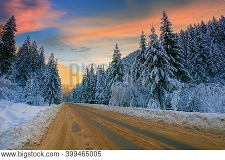 Road Through Mountain Landscape In Winter. Spruce Forest Covered In Snow. Dramatic Sky With Clouds G