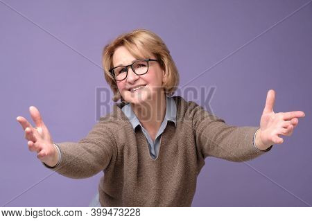 Cheerful European Mature Woman Welcoming You With Her Arms Outstretched Out.