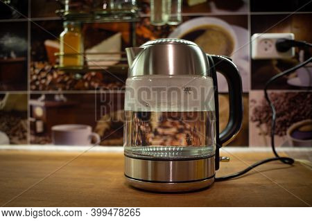 An Electric Kettle Is In The Kitchen. The Kettle Is Filled With Water. A Transparent Kettle With Wat