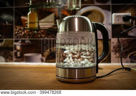 A Boiling Electric Kettle Stands On A Brown Table. The Kettle Is Plugged In. A Transparent Kettle Bo