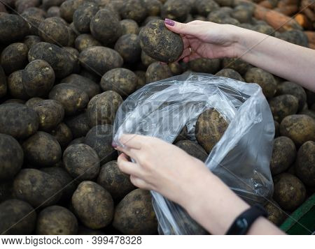 Female Hands Put Potatoes In A Package. Buying Potatoes At The Supermarket. Showcase With Freshly Du