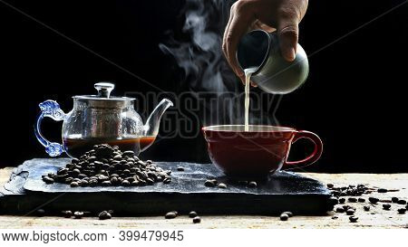 Man's Hand Pouring Milk Into Red  Coffee Cup With Steam, Coffee Beans And Coffee Pot On Black Slate