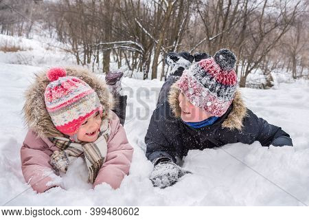 Happy Children Play In A Snowdrift In Winter. Winter Vacation And Holidays.