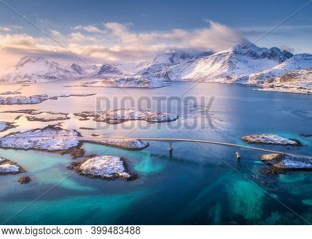 Aerial View Of Bridge Over The Sea And Snowy Mountains In Lofoten Islands, Norway. Fredvang Bridges