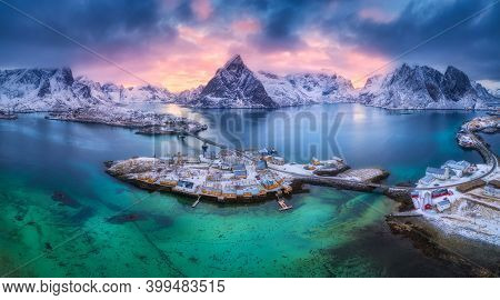 Aerial View Of Blue Sea, Snowy Mountains, Rocks, Village, Buildings, Rorbu, Road, Bridge, Colorful C