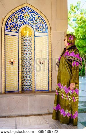 A woman dressed in a traditional omani abaya looking at an ornate alcove at the Sultan Qaboos Grand Mosque in Muscat, Oman