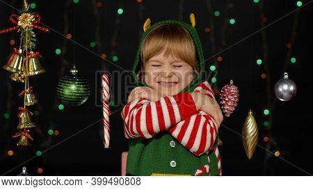 Little Fun Blonde Kid Teen Teenager Girl In Christmas Elf Santa Helper Costume Hugging, Embracing. J