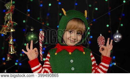 Child Smiles To Camera With Ok Gesture. Blonde Teen Kid Girl In Christmas Elf Santa Claus Helper Cos