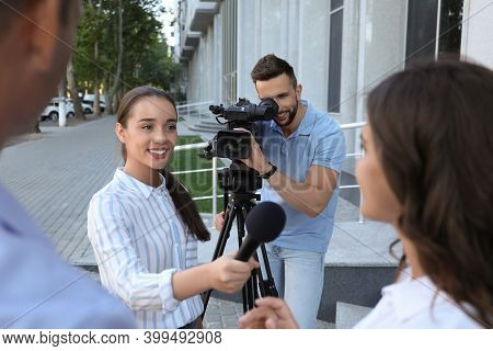 Professional Journalist And Operator With Video Camera Taking Interview Outdoors