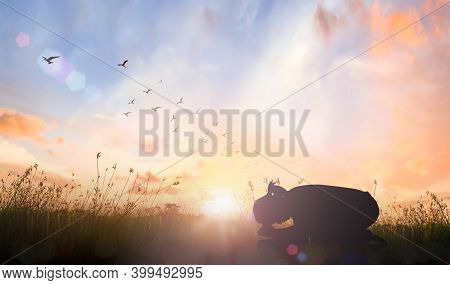 Worship God Concept: Silhouette Of Prayer Woman Bow Down And Praying Over Meadow Sunset Background
