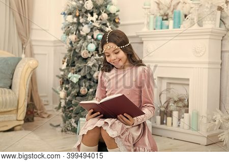 Reading Days Of Christmas. Cute Little Girl Read Book At Christmas Tree. Adorable Small Child Enjoy