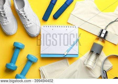 Flat Lay Composition With Sportswear, Notebook And Dumbbells On Yellow Background. Gym Workout Plan
