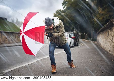 Man With Colorful Umbrella Caught In Gust Of Wind On Street