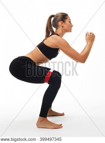 Strength and motivation. Sporty young woman squatting doing sit-ups with resistance band.