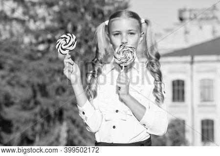 Lollipop Melting In Your Mouth. Happy Child Eat Lollipop Summer Outdoors. Enjoying Large Swirl Lolli