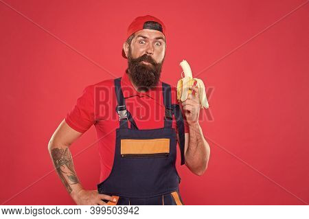 Healthy Break Concept. Brutal Male In Cap And Uniform Eat Banana. Healthy Lunch Snack. Mature Man Bu
