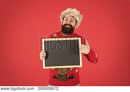 His Barber Gets Thumbs Up. Happy Hipster Hold Empty Blackboard. Bearded Hipster In Winter Wear. Hips