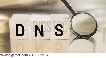 Dns Abbreviation Of The Domain Name System Concept On Wooden Cubes, Next To A Magnifying Glass On A