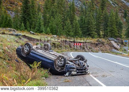 Car Accident Place On A Bend, Overturned Car Lies On The Roof,