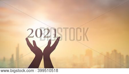 New Year 2021 Concept: Silhouette Hands Show 2021 Against Blurred City Sunrise Background. Bangkok,