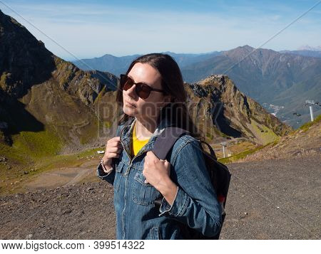 Young Female Tourist With A Backpack Is Walking In The Mountains, Traveling In National Parks. Local