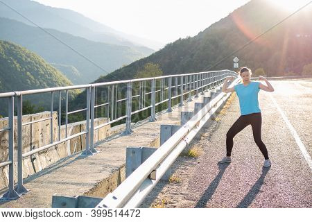 Warm Up In The Morning In The Mountains. Funny Young Woman Jumping And Doing Exercises, A Morning Jo