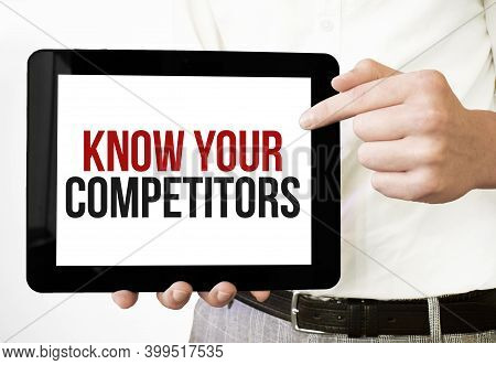 Text Know Your Competitors On Tablet Display In Businessman Hands On The White Bakcground. Business