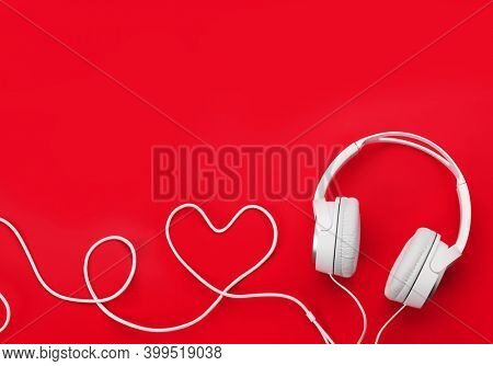 Headphones with heart shaped cable over red backdrop. Love music or Valentines day concept. Top view flat lay with copy space