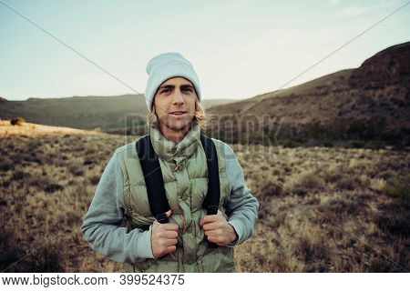 Happy Male Teen Hiking In Luscious Mountain Dressed Warmly Reading To Exercise