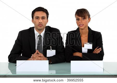 Two businesspeople wearing visitor badges