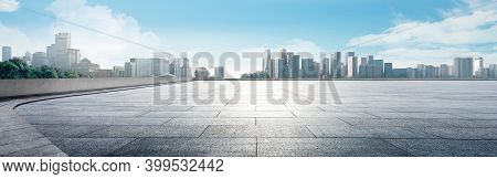 Panoramic Skyline And Buildings With Empty Space Dark Concrete Square Floor. Sunrise Over The Modern