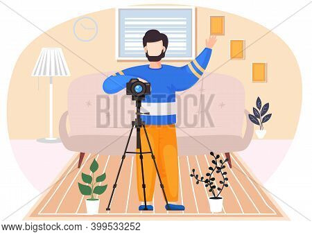 The Guy Standing And Raising His Hand Up. Photographer With A Camera And A Tripod In The Apartment.