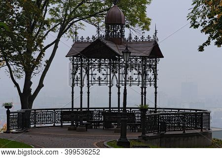 Scenic Foggy Landscape Of Autumn Park With Viewing Platform. Beautiful Metal Arbor With Wooden Bench