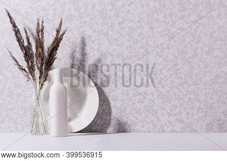 Elegant Home Decor With White Ceramic Crockery, Glass Bottle And Grey Bouquet With Dried Grass On Wh