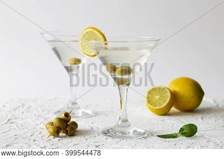 Martini With Lemon. Two Martini Glasses With Cocktail And Olives On White Background. Cocktail Marga