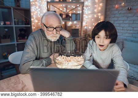 Grandfather And Grandson Are Watching Video On Laptop At Table At Night At Home. Grandfather In The