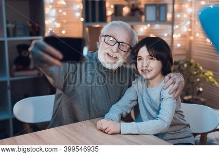 Grandson And Grandfather Are Sitting At The Table And Watching A Movie With Popcorn. Grandson Closes
